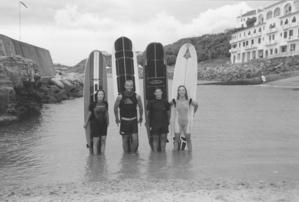 surfers with boards black and white